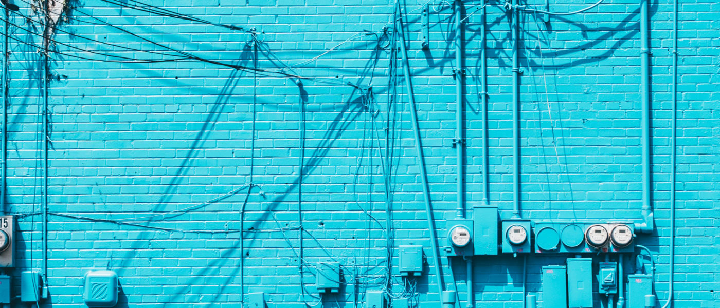 A blue wall with criss-crossed cables and wires.