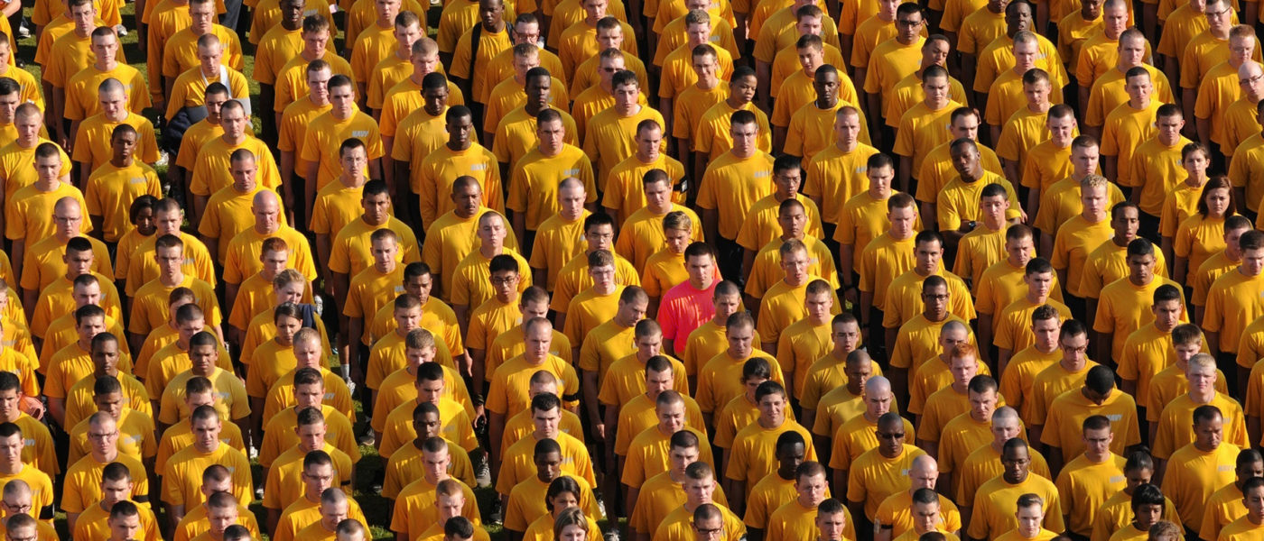 A crowd of men in yellow shirts. One man in a red shirt.